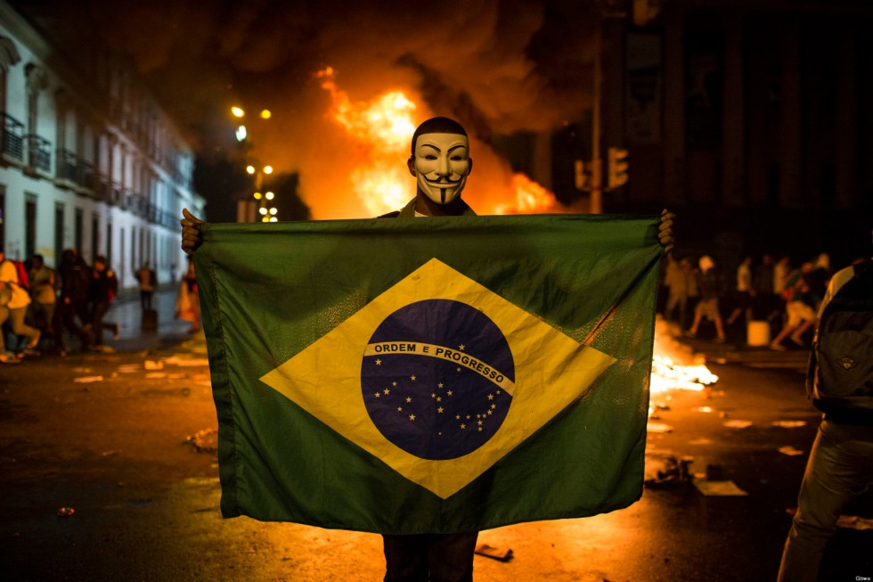 A demonstrator holds a Brazilian flag in front of a burning barricade during a protest in Rio de Janeiro in Rio de Janeiro, Brazil, Monday, June 17, 2013.